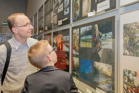 Jozefow, Poland - February 02, 2017; Dad and son watching an exhibition of photos during the vernissage