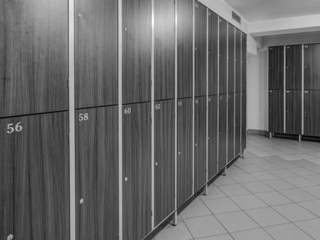 The row of wooden cabinets  in a fitness club dressing room