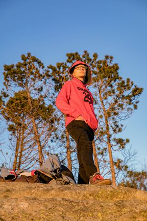 Boy in a red hoodie on the rock.