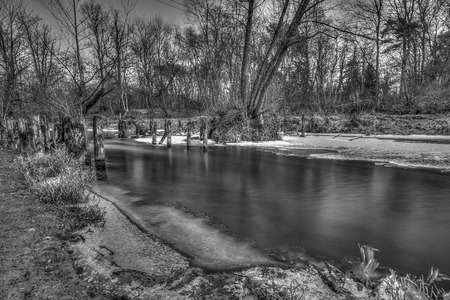The Swider River in the winter season and the remnants of the wooden bridge in Jozefow