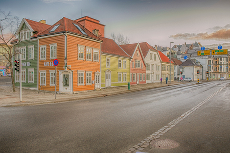 Bergen, Norway - February 12, 2017:  Yellow, green and white wooden houses with tiled roofs in Scandinavia