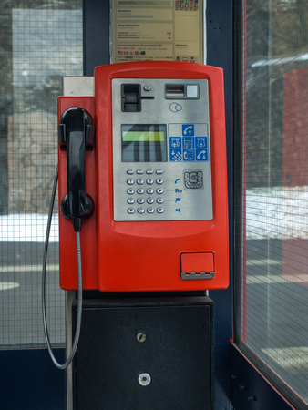 Oslo, Norway - February 16, 2017: A red telephone booth on a street in Oslo