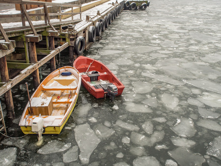Oslo, Norway - February 16, 2017: Small motor-driven boats with paddles on the frozen fjord water in Oslo.