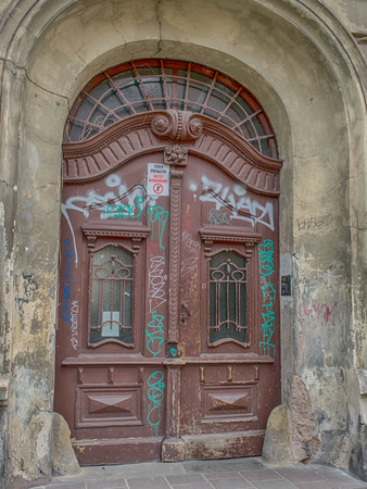 Cracow, Poland - April 03, 2017: Wooden, decorative and a little damaged and painted door to a old house in Cracow
