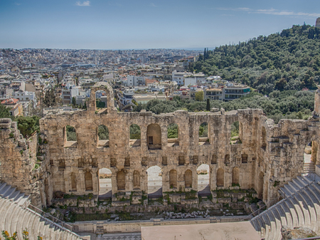 Athens, Greece - April 03, 2015: The Odeon of Herodes Atticus - stone theatre structure located on the southwest slope of the Acropolis of Athens, in the background urban area of Athens
