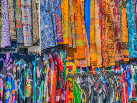 The multi-coloured colourful silk scarves hanging in on stall in the sunlight