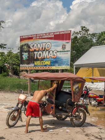 Santo Tomas, Peru - May 17, 2016: Man is washing a rickshaw in the river in the small village
