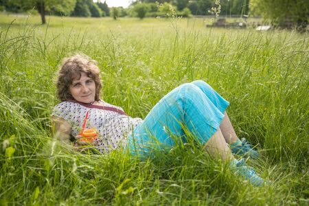 The woman is lying in the high grass with a glass