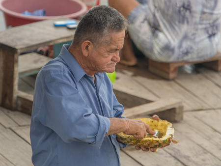 Caballococha, Peru - Dec 11, 2017:  Portrait of a man eating pineapple by the spoon.