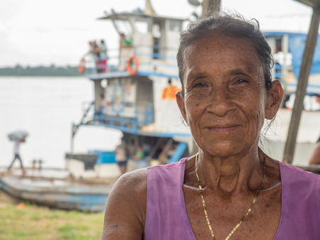 Caballococha, Peru- Dec 11, 2017:  Portrait of a woman with a red skin on the background of cargo boat in the Amazon  jungle 報道画像