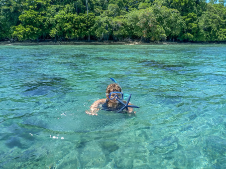 Woman snorkeling in the turquoise sea and hold blue starfish, Seven Islands, Seram Island, Indonesia