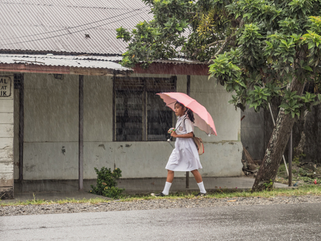 Ambon, Indonesia - February 12, 2018: Children in the white uniforms coming back from the school in the heavy rain