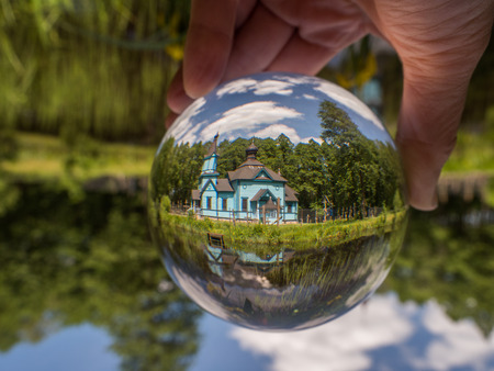 Koterka, Poland - May 20, 2018: Blue, wooden orthodox church reflecting in the glass ball. Podlachia region,