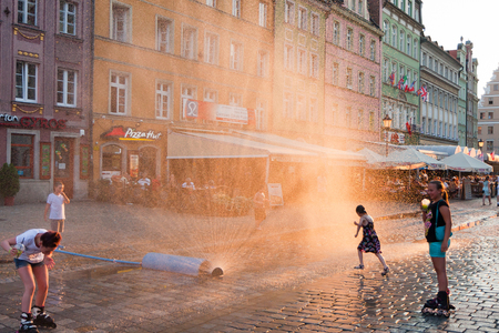 Wroclaw, Poland - July 19, 2014: Children playing near the water wall on Wroclaw street during the very hot day