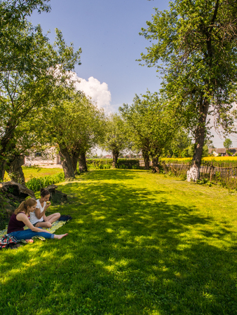 Zalipie, Poland - May 20, 2017: Two young girl are sitting in the spring garden surrounded by weeping willows Standard-Bild