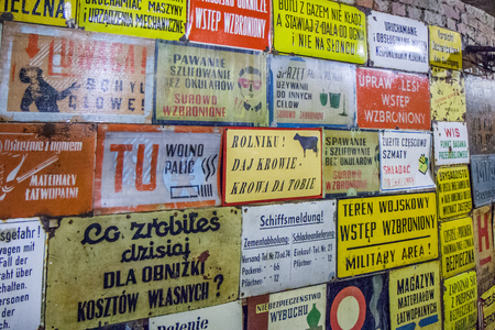 Various old, yellow information boards with various warnings