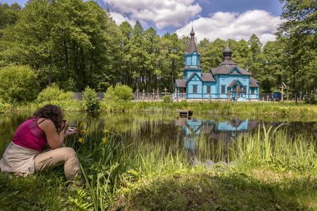 A woman takes picture of  blue, wooden orthodox church.  Podlasie. Podlachia. Poland, Europe. The region is called Podlasko or Podlasze 版權商用圖片