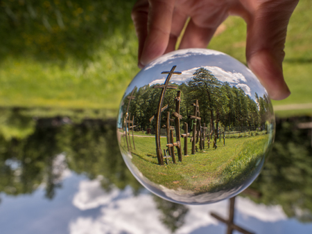 Wooden crosses reflecting in the glass ball. Koterka. Podlachia region.