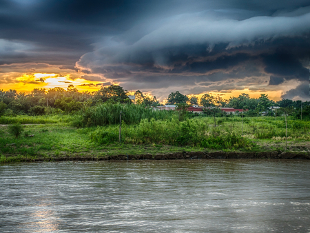 Sunset and dramatic clouds before the storm on the sky over the Amazon river, Amazonia, Santa Rosa, Peru. Stock Photo