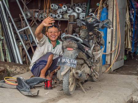 Jakarta,  Indonesia - February 20, 2018: Happy man repairing the motorcycle (ojek) on the street of Jakarta. 新聞圖片