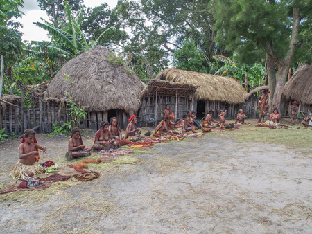 Wamena, Indonesia - January 23, 2015: Dani tribe women and men selling coteka and other local  handicraft in front of her wooden huts