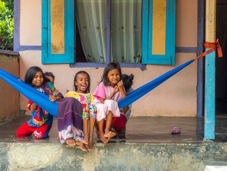 Ambon, Indonesia - February 11, 2018: A group of young Indonesian girls, in colorful clothes sitting on the hamak in the small village on the island, Maluku, Maluki