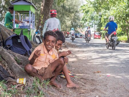 Kaimana, Indonesia - February 10, 2018: A group of Indonesian, children in brown uniform siting on the steet in the small village on the West Papua