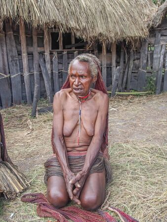 Wamena, Indonesia - January 23, 2015: Dani tribe woman selling coteka and other local  handicraft in front of her wooden hut