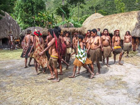 Wamena, Indonesia - January 23, 2015: Dani tribe women dancing in the front of their house