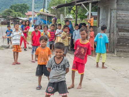 Ambon, Indonesia - February 11, 2018: A group of Indonesian, preschool children in colorful clothes in the small village on the island, Maluki, Maluku