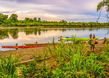 Jungle, Indonesia - January 13, 2015: Colourful boats  on the banks of the river during the sunset. Publikacyjne