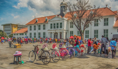 Jakarta, Indonesia - January 11, 2015: Coloured bikes and people in colourful costumes at Fatahillah Square in Jakarta Editorial