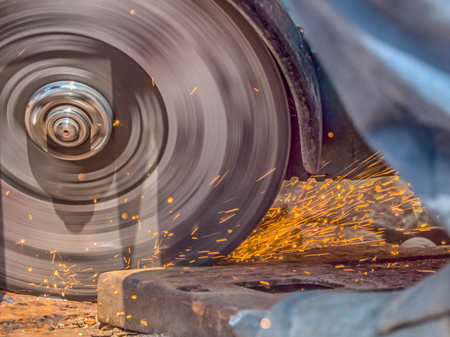 A grinder is grinding quickly and sparks are flying around