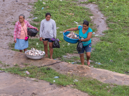 Tabatinga, Brazil - September 15, 2018: Women are selling the fishes during rainy day in the port of Amazon river. Tres Fronteras. Latin America. Amazonia.