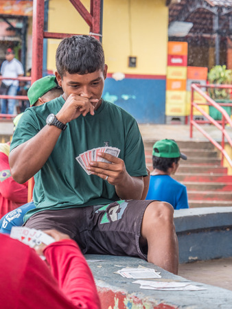 Tabatinga, Brazil - September 15, 2018: Brazilian man is playing the cards during a rainy day at the port of the Amazon. Tres Fronteras. Latin America. Amazonia.