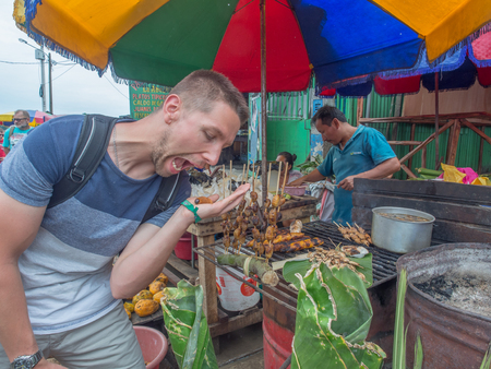 Happy tourist is tasting fresh worm on the local bazaar in Iquitos, Peru. Latin America