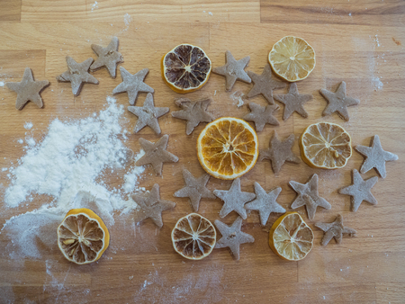 Background, texture. Dried orange slices and baked gingerbread  are waiting for Christmas on wooden table.