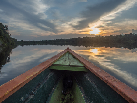 Paumari, Brazil- December 07, 2017: Traditional, indian boat and beautiful view with the reflection in the lagoon of Amazon jungle. during sunset. Latin America