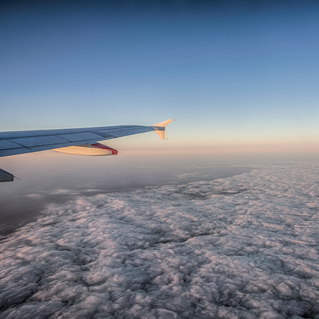 Wing of the plane over the clouds during the sunrise