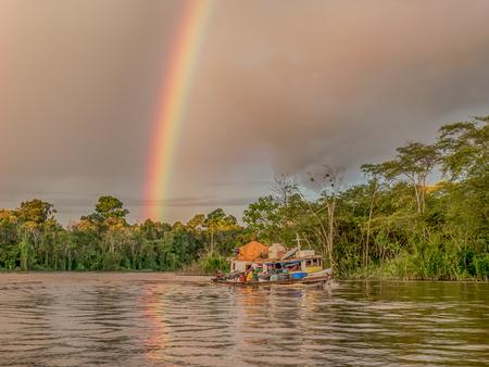 Border of Peru and Brazil - May 05, 2016: Rainbow over the boat on Amazon river Latin America. Javarii River. Yavarii River.