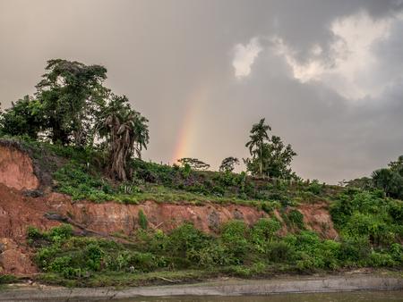 Amazon River, Peru  - May 15, 2016: Rainbow over the bank of Amazon river Latin America.