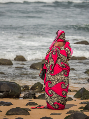 A figure of a Muslim woman in a red boubou praying at the ocean shore. Senegal. Africa. Stock Photo
