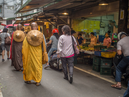 New Taipei City,Taiwan - October 04, 2016: Buddhist monks praying and collecting  donations on  a local market Editorial