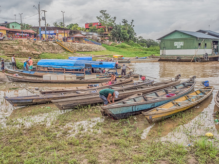 Tabatinga, Brazil - November 25, 2018: People and wooden boat in  the port of Amazon river. South America. Amazon River.  Tres fronteras. Rain Forest of Amazonia.