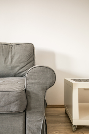 Grey sofa and white table on the background of white wall