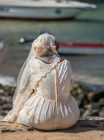 View of Senegalese woman in a white wedding dress sitting by  the ocean on  island of Goree, Reklamní fotografie