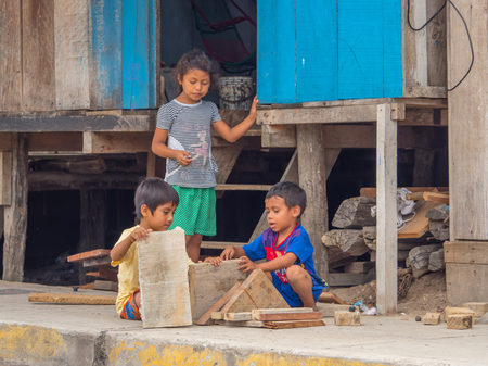 Belen, Iquitos, Peru - September 25, 2018: Two boys playing with pieces of wooden boards on the street. South America 에디토리얼