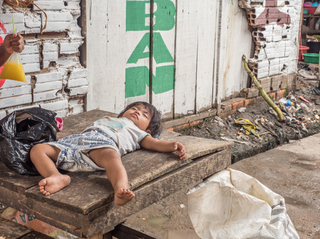 Belen, Iquitos, Peru - March 27, 2018: Young woman selling bananas on the Belem Market in Iquitos and the child is sleeping on the wooden table. Belén. Editorial