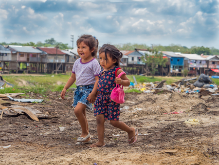 Belen, Iquitos, Peru - September 25, 2018: Two girls walking on the street in the poorest district of Iquitos, Belen, South America