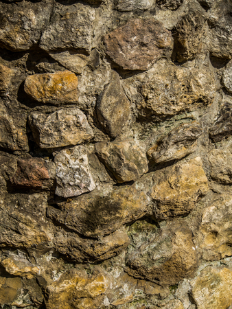 Background. The wall of multi-coloured stones agglomerated with cement mortar